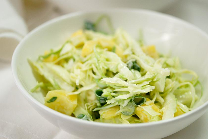 Spitzkohl Salat mit Apfel und Mango in weißer Schüssel
