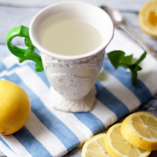 Tasse mit Wasser mit frisch gepresstem Zitronensaft