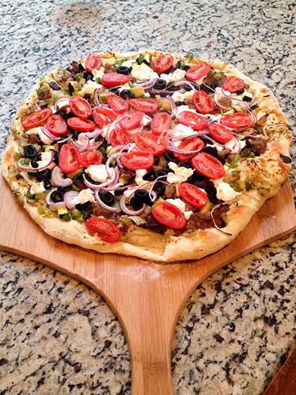 Pizza auf dem Grill, BBQ-Pizza mit Tomaten, Oliven, selbstgemachtem Teig auf der Pizzaschaufel