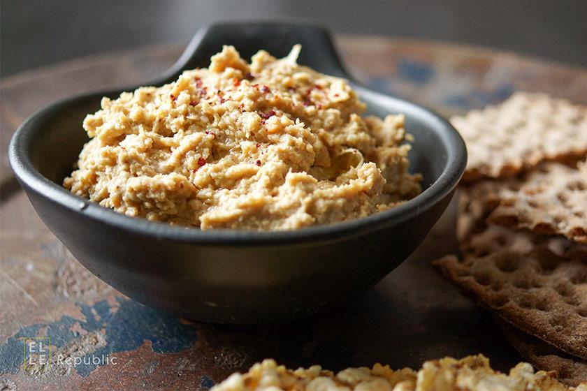 Hummus mit Sumach, Tahini, Zitronensaft, Cayenne-Pfeffer, Kichererbsen in schwarzer Schüssel