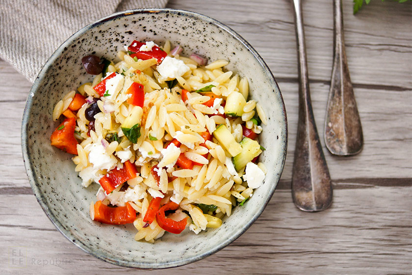 Mediterranean orzo pasta salad recipe with artichokes, pointed red pepper, zucchini, olives, sun-dried tomatoes and feta cheese.