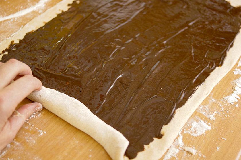 Osterzopf Teig mit schokolade bestreichen, glatt streichen und zusammenrollen.