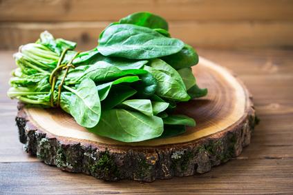 Frischer Spinat auf Holzbrett