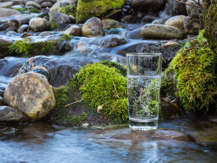 Warum Wasser trinken wichtig ist, Glas Wasser in Fluss