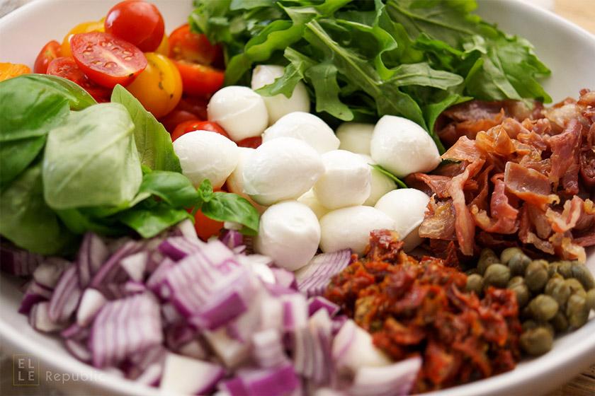 Sommer Nudelsalat Rezept mit Tomaten, süße, rote Zwiebeln, Basilikum, Rucola, sonnengetrocknete Tomaten, Kapern und Parmaschinken mit Balsamico-Olivenöl-Dressing.