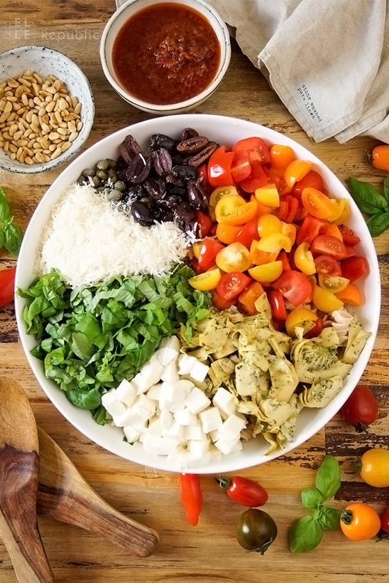 Zutaten Caprese Nudelsalat mit Antipasti, Artischocken, Oliven, Tomaten, Mozarella, Basilikum
