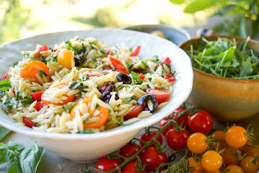 Rezept für Cherry-Tomaten-Nudelsalat mit Paprika und Oliven. Orzo Reisnudeln Dazu Petersilie, frischer Basilikum, Rucola und Zitronenschalen und Zitronensaft.