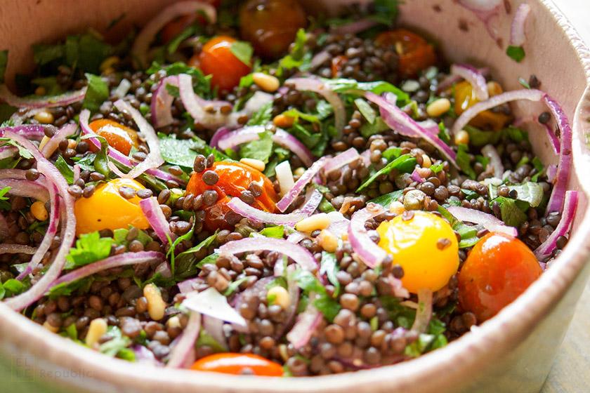 Linsensalat mit gerösteten Tomaten Rezept mit Beluga-Linsen, Kapern, Zitrone, Pinienkernen und Kräutern. Glutenfrei und vegetarisch.