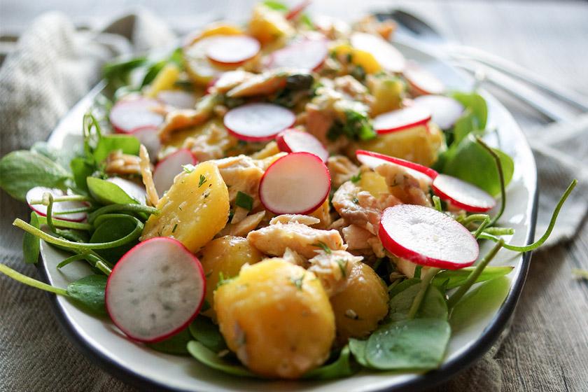 Kartoffelsalat mit Räuchersaibling Rezept. Jungen Kartoffeln, frischem Postelein (Portulak), Kapern, Frühlingszwiebel und Radieschen, mit einem Dressing aus Zitronensaft, Meerrettich, Dill und Olivenöl