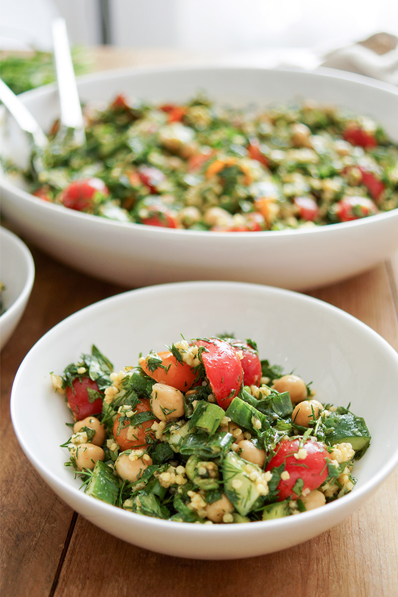 chickpea tabbouleh salad with millet, chickpeas, tomatoes, cucumber, green onions, parsley, dill and mint