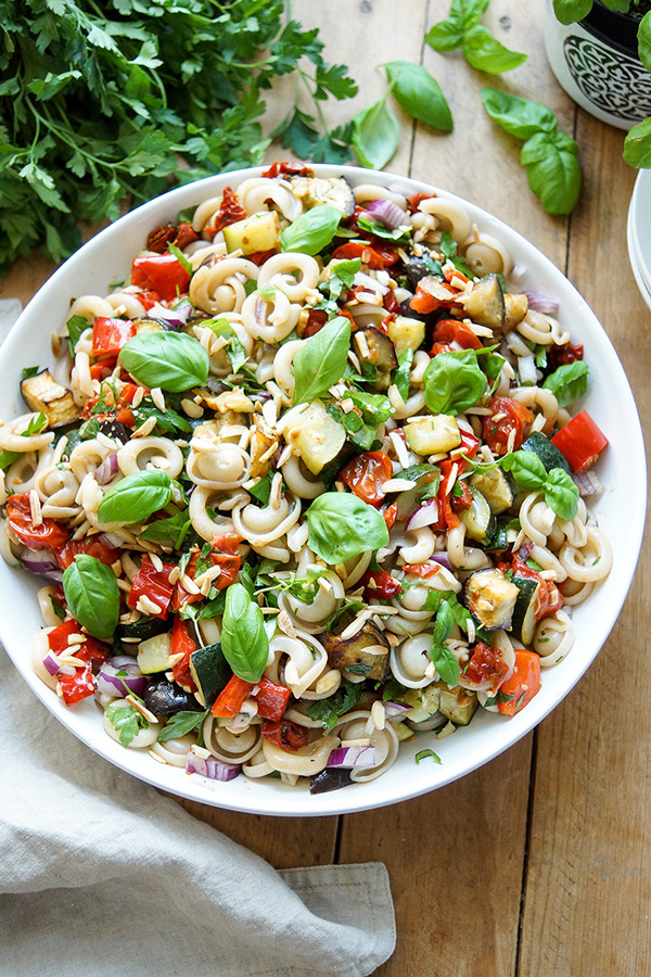 a healthy vegan summer roasted vegetable pasta salad recipe featuring red peppers, zucchini, eggplant and cherry tomatoes in a balsamic dressing