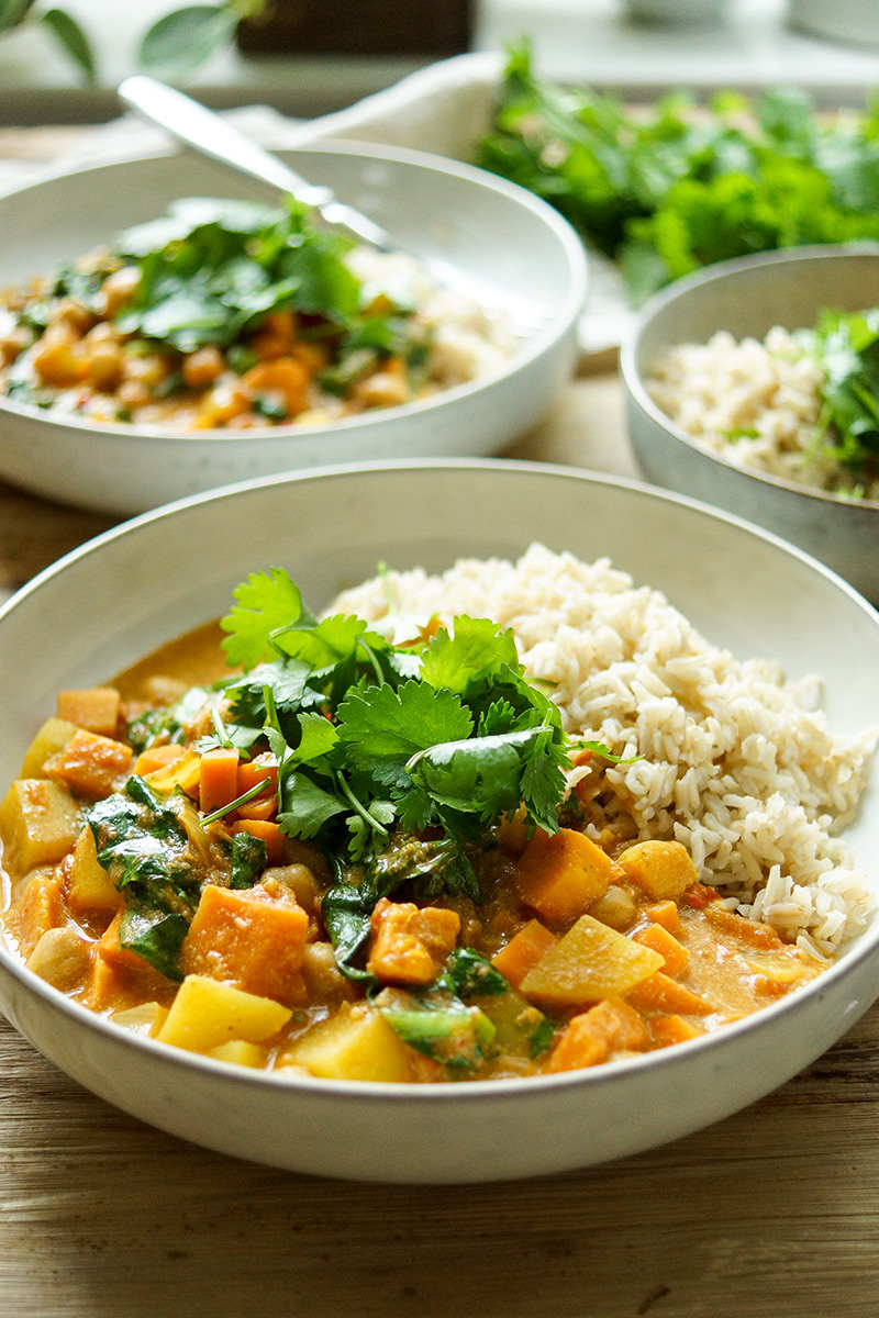 Coconut Chickpea Curry with Sweet Potato and Spinach, in bowl with basmati rice