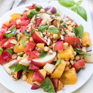 Nektarinensalat mit Tomaten alte Sorte, Kichererbsen, roter Zwiebel, gerösteten Mandeln, Basilikum und Minze. Vegan