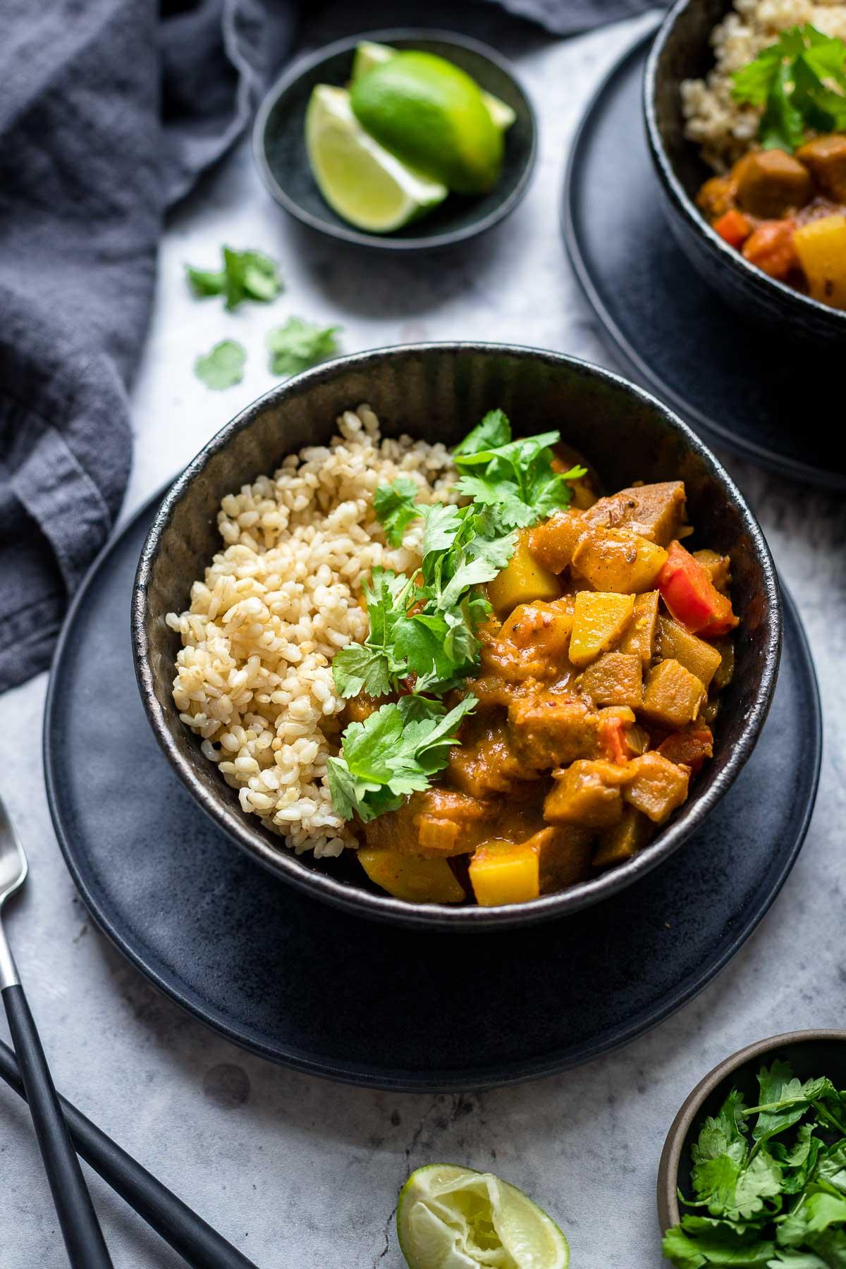 Indisches Auberginen Kartoffel Curry mit Tomaten und Kokosmilch Rezept, serviert mit Vollkornreis, Koriander und Limetten