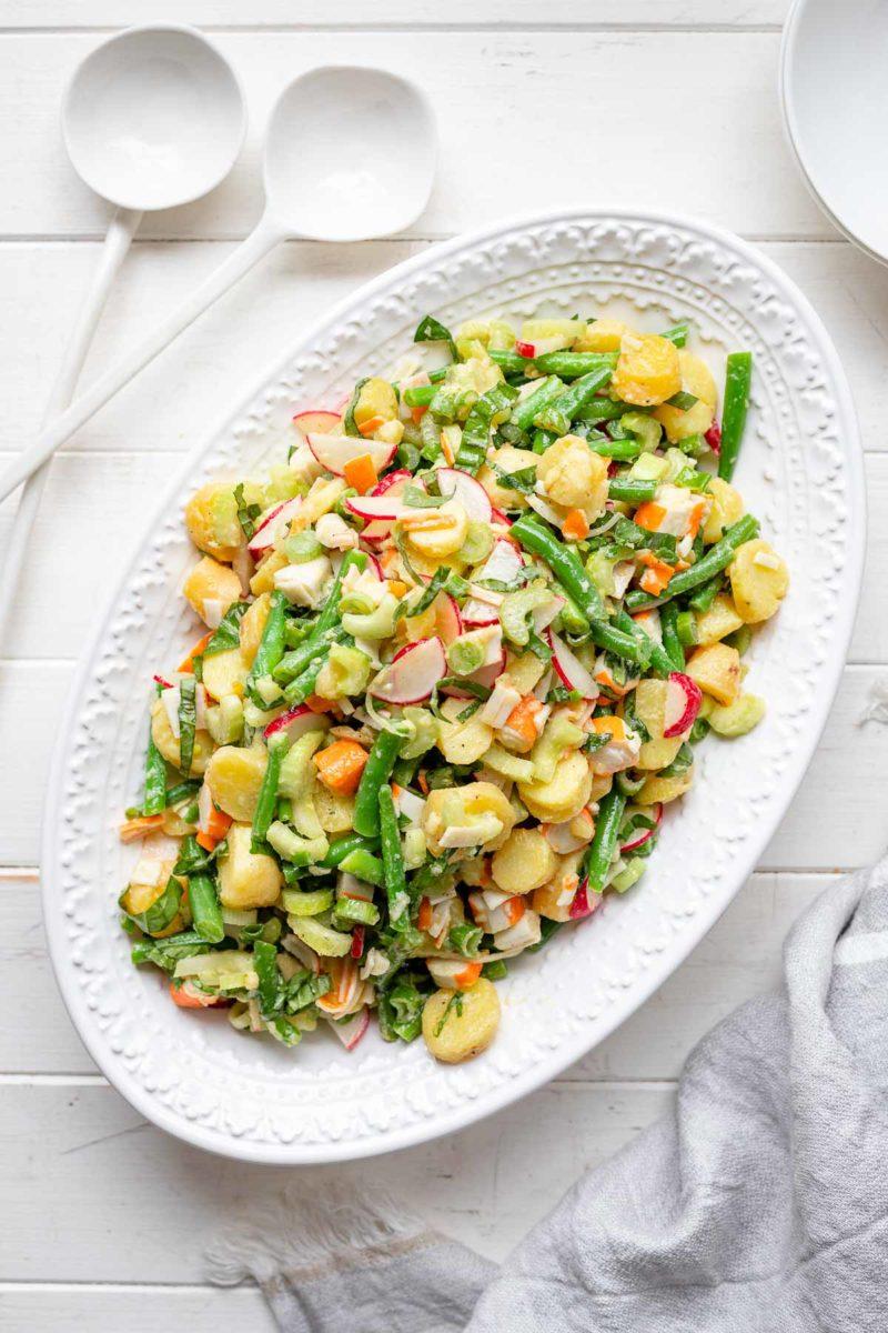 Einfacher Kartoffelsalat mit Surimi, grüne Bohnen, Sellerie und Radieschen in Öl Essig Dressing